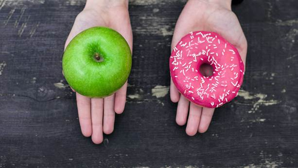 Outstretched hands holding green apple and donut