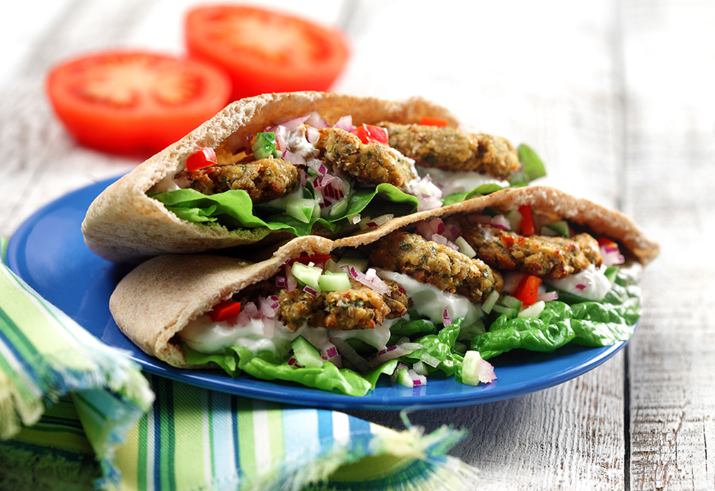 Pita bread filled with falafel, lettuce, tzatziki, tomatoes, onion and cucumber
