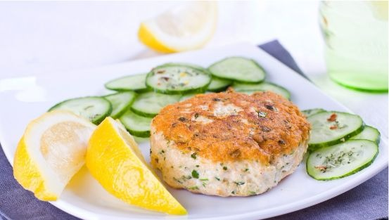 Salmon patty on plate with sliced cucumber and lemon wedges