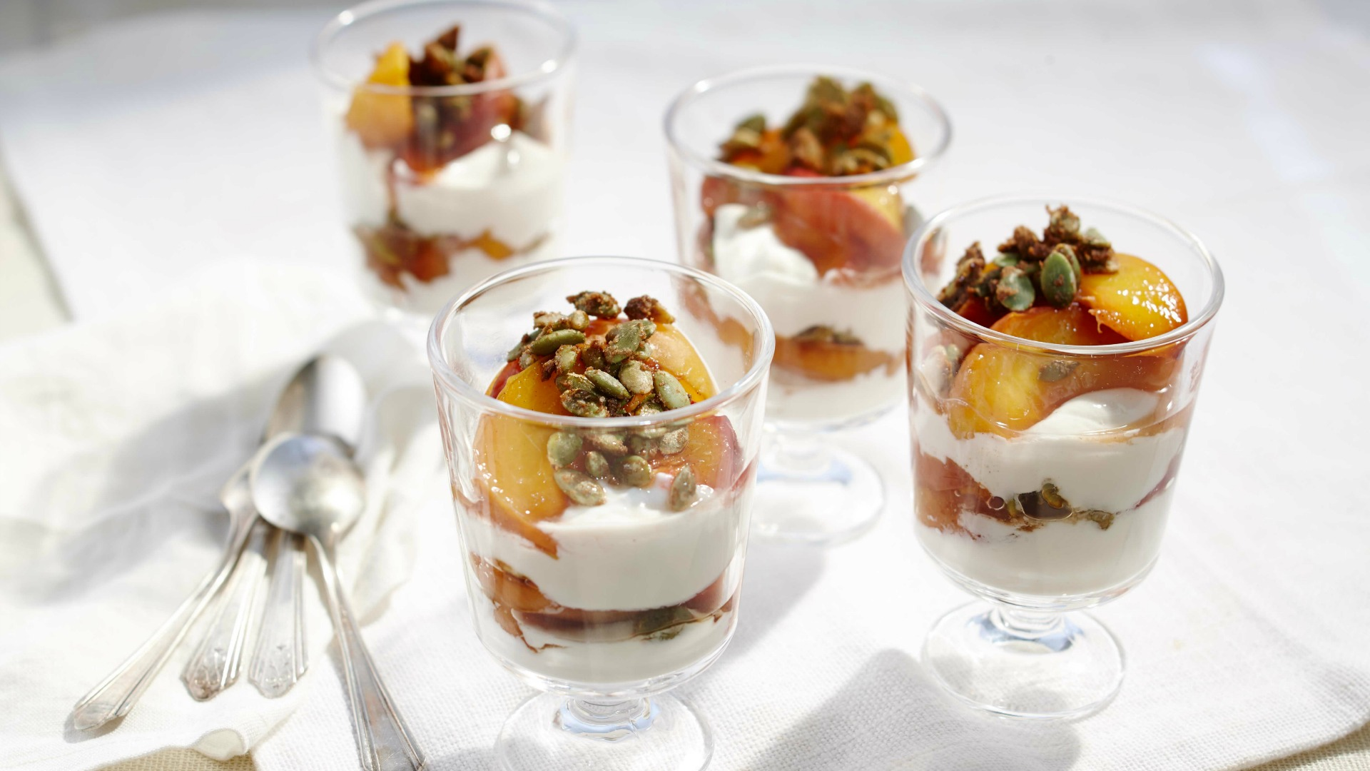 Four glasses filled with yogurt, sliced roasted peaches and pumpkin seeds