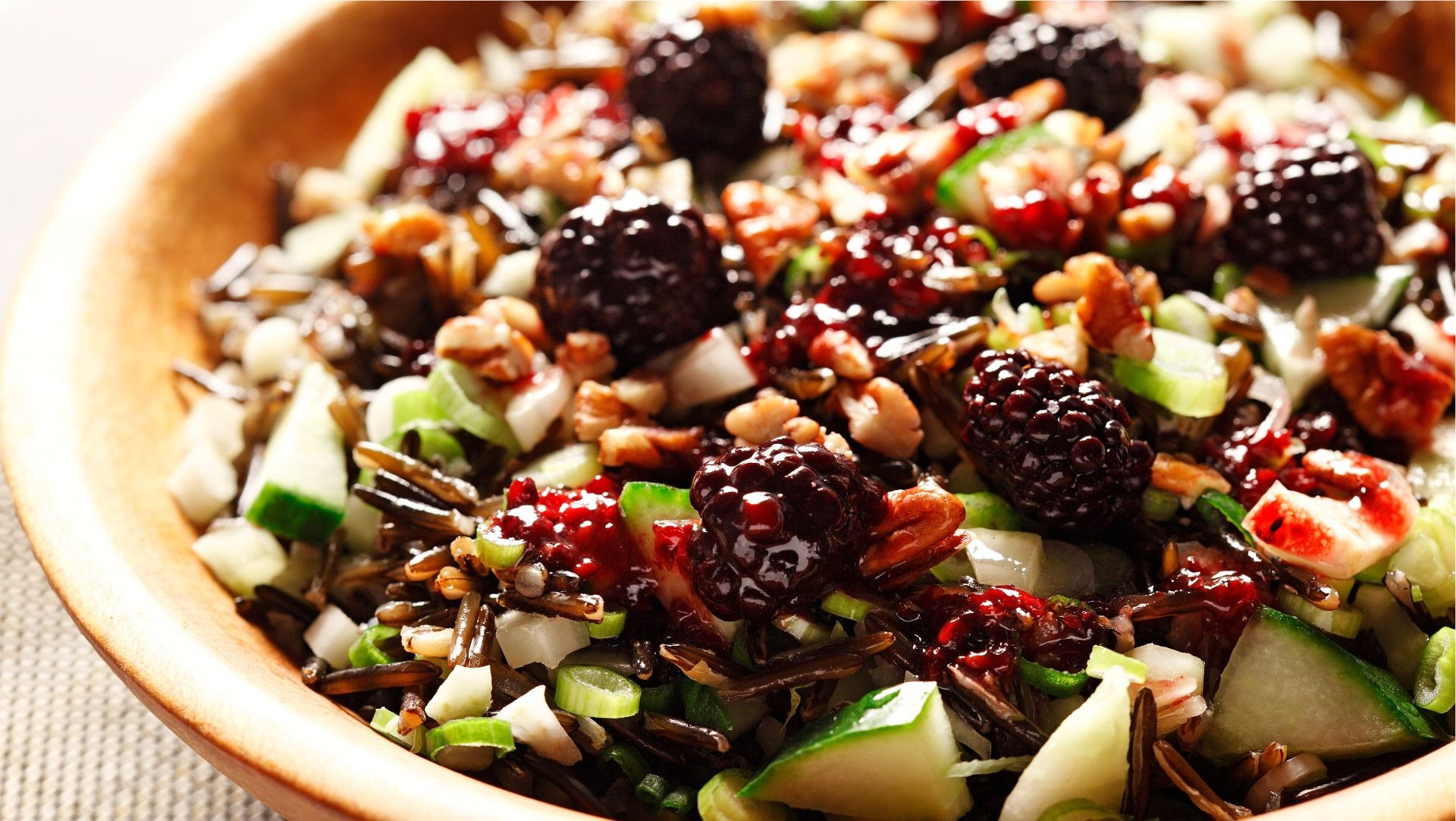 Crunchy wild rice salad with blackberry dressing in a wooden bowl.
