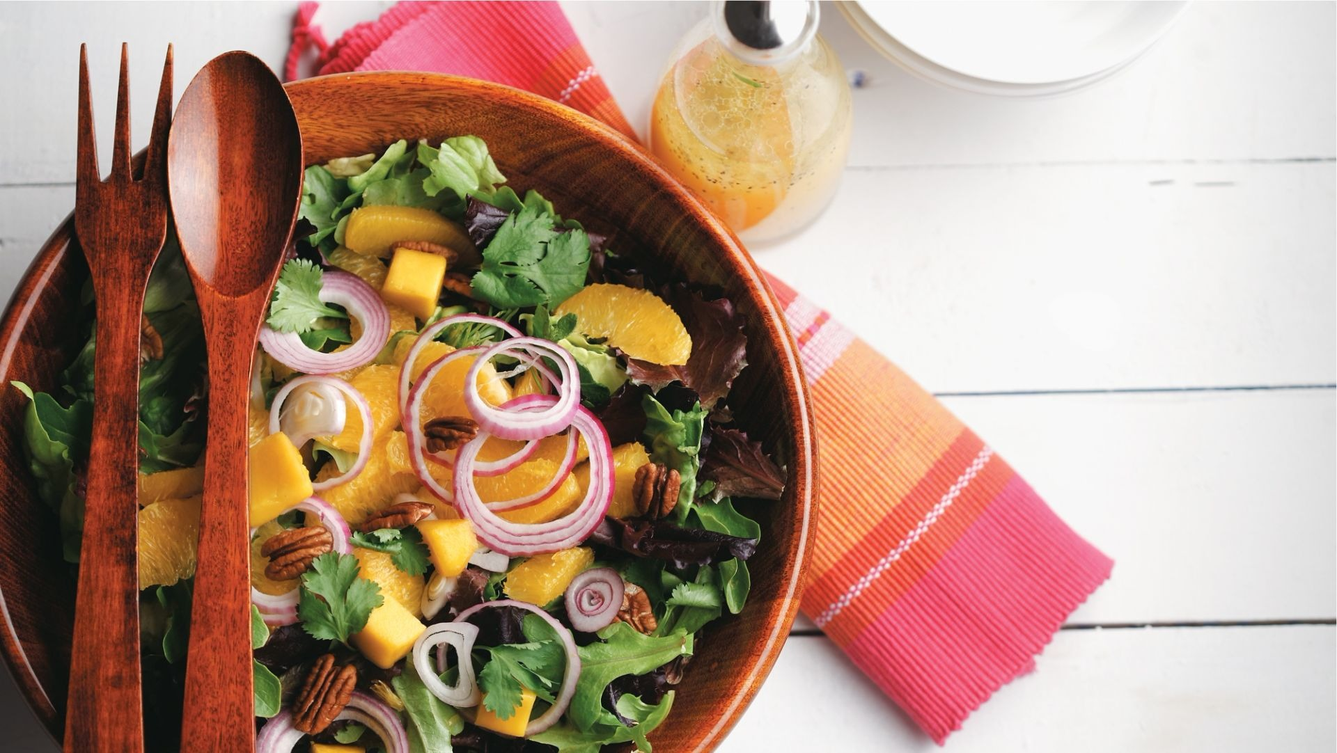Mixed greens, mango and pecan salad in a wooden bowl with wooden utensils.