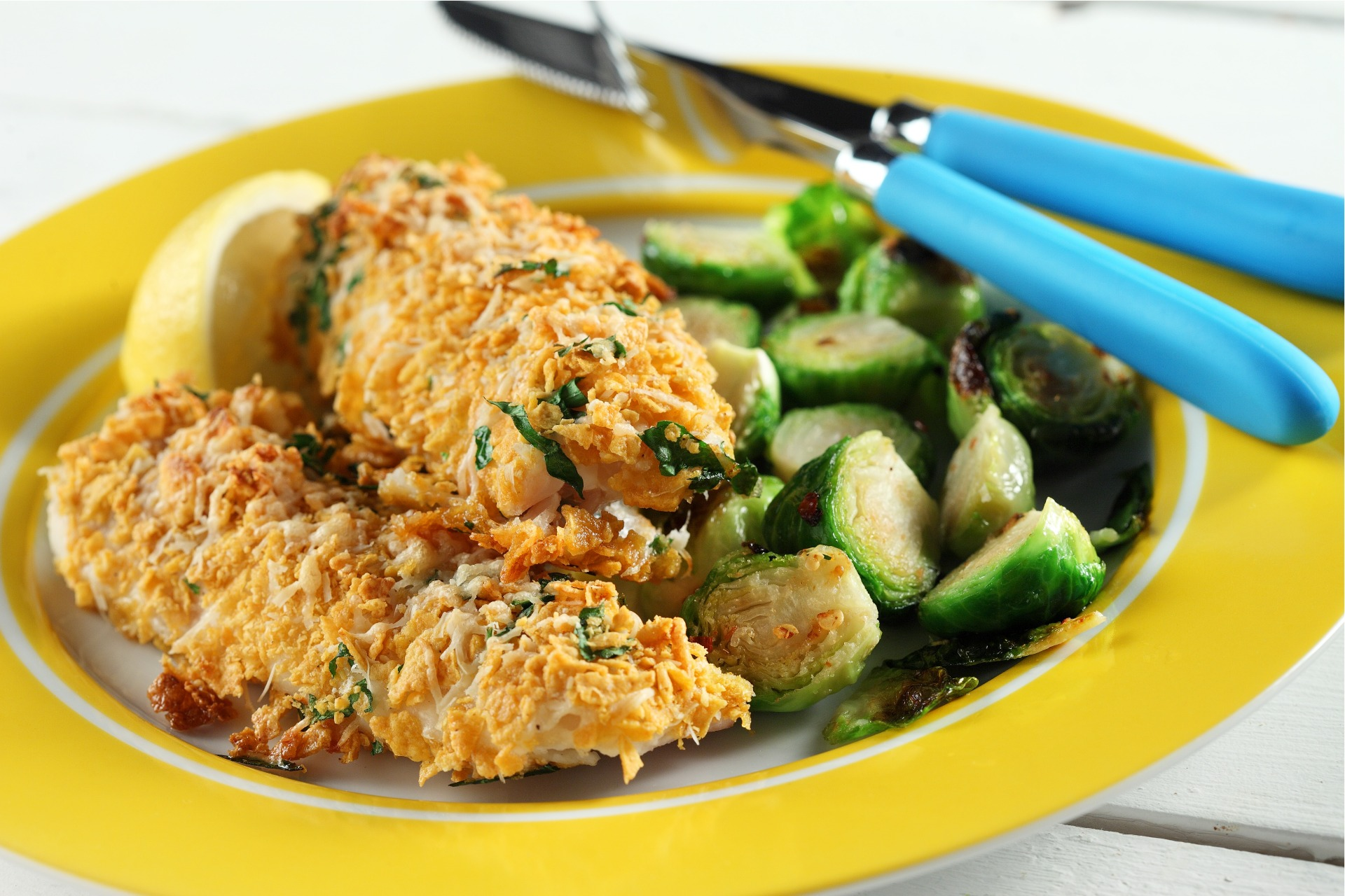 Plate with two pieces of battered halibut fillets, cooked brussel sprouts and sliced lemon wedge