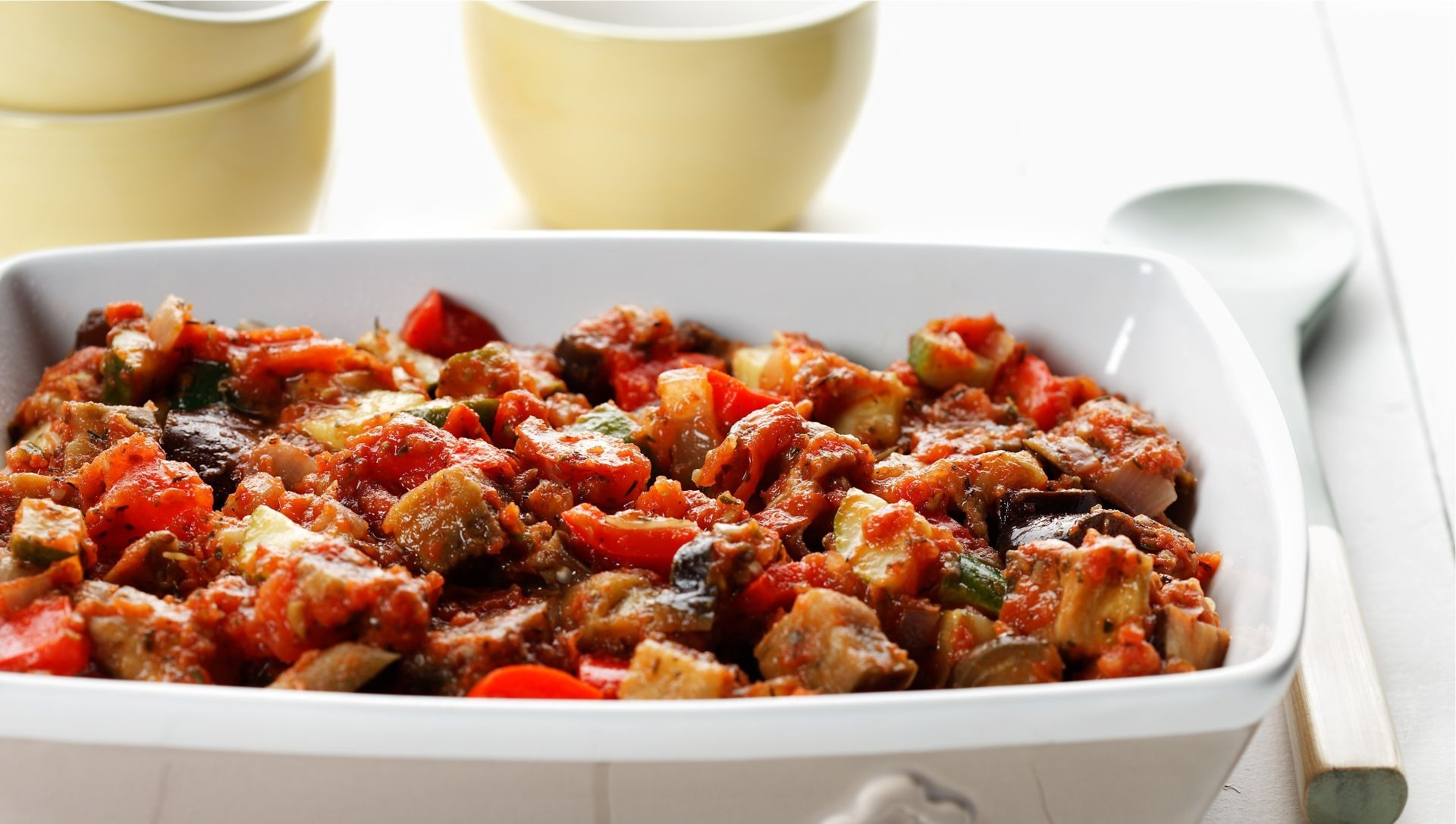 Quick ratatouille in a white baking dish with a serving spoon on the side.