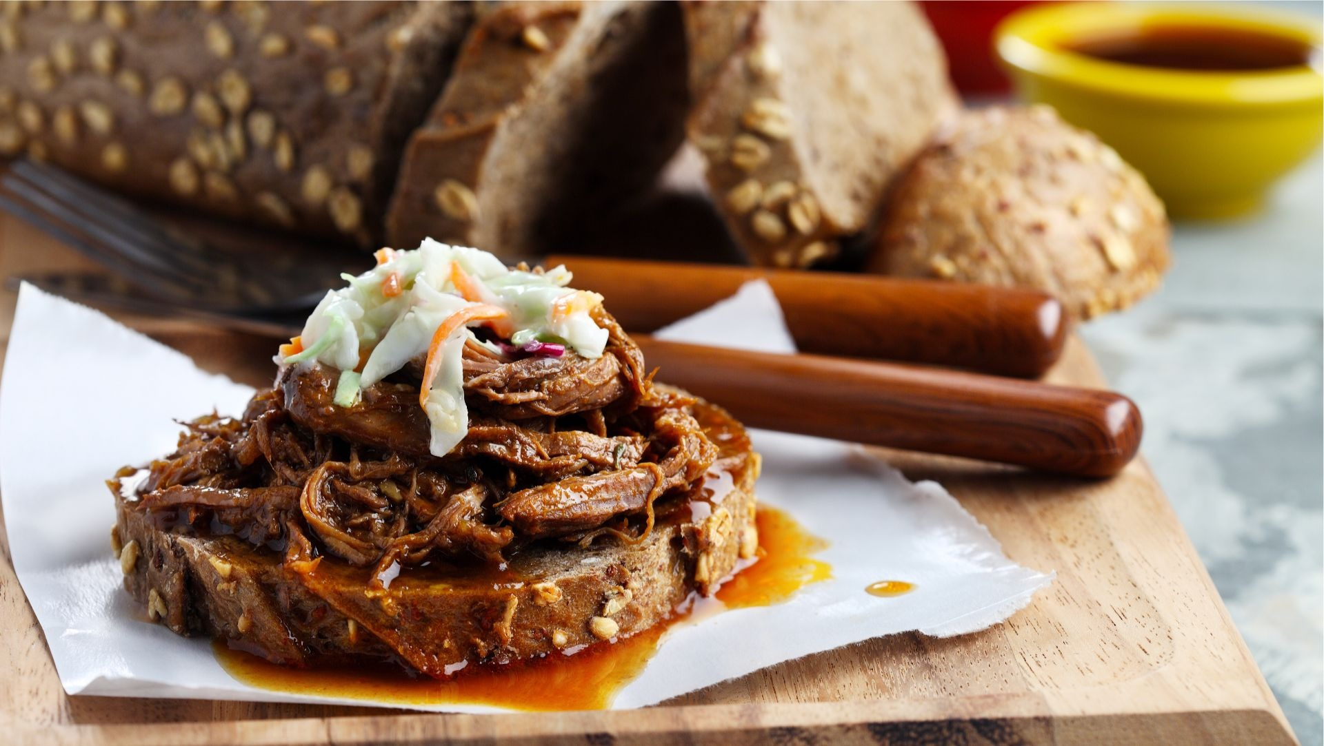 Shredded beef brisket on slice of multigrain bread topped with coleslaw