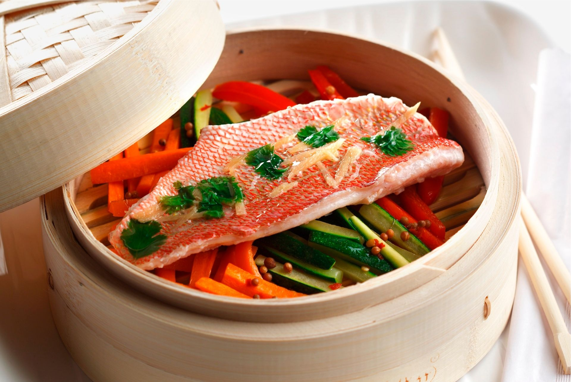 Snapper fillet resting on julliened zucchini, red pepper and carrots in a bamboo steamer