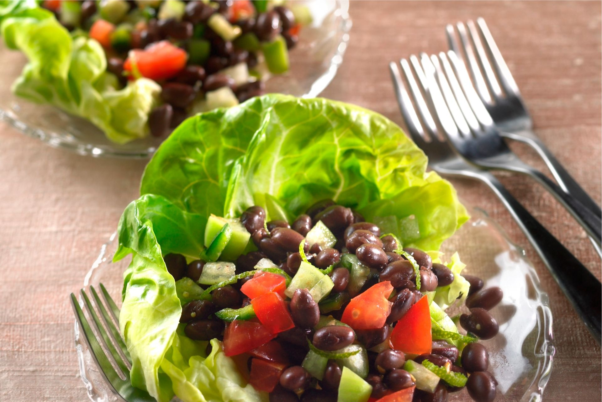 Lime-zested tomatillo-black bean salad on lettuce leaves.