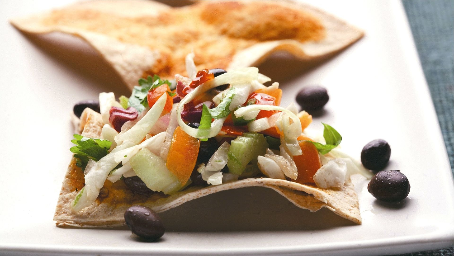 Zesty coleslaw with tortilla triangles on a white plate.