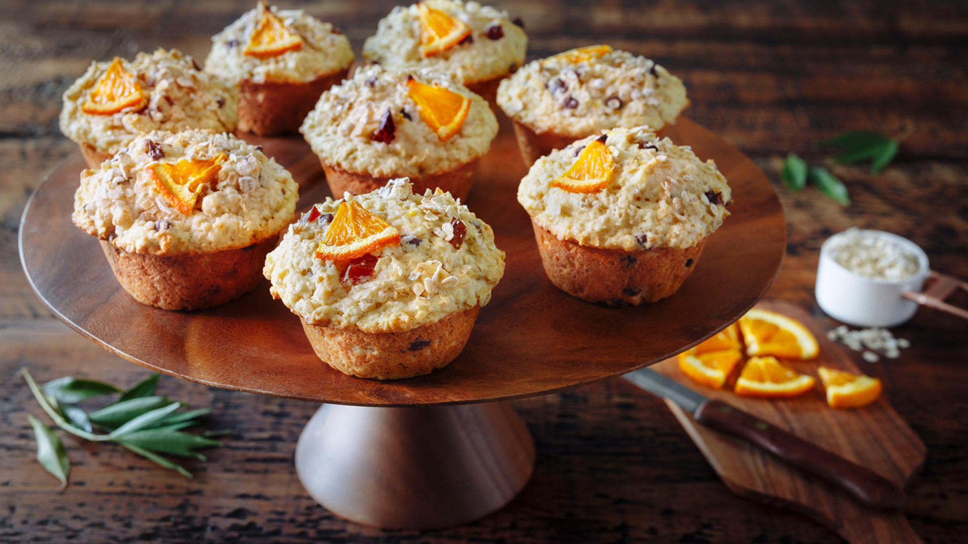 Eight oatmeal and orange muffins on a wooden serving tray