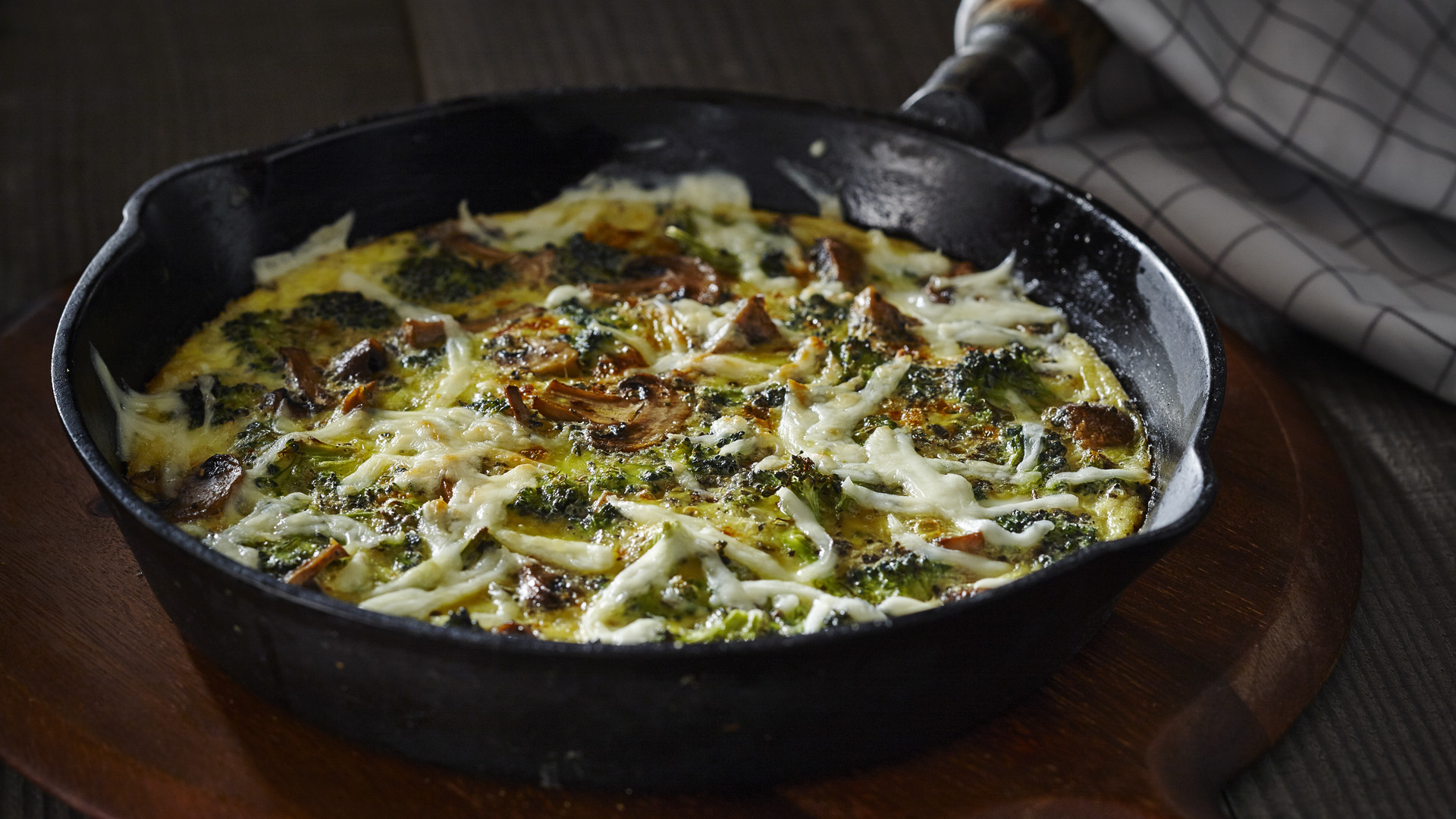 Broccoli and mushroom frittata with shredded mozzarella in a skillet