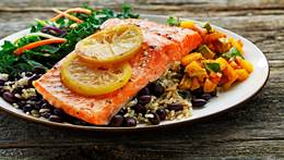Plate of roasted trout, mango salsa, rice, black beans and green salad