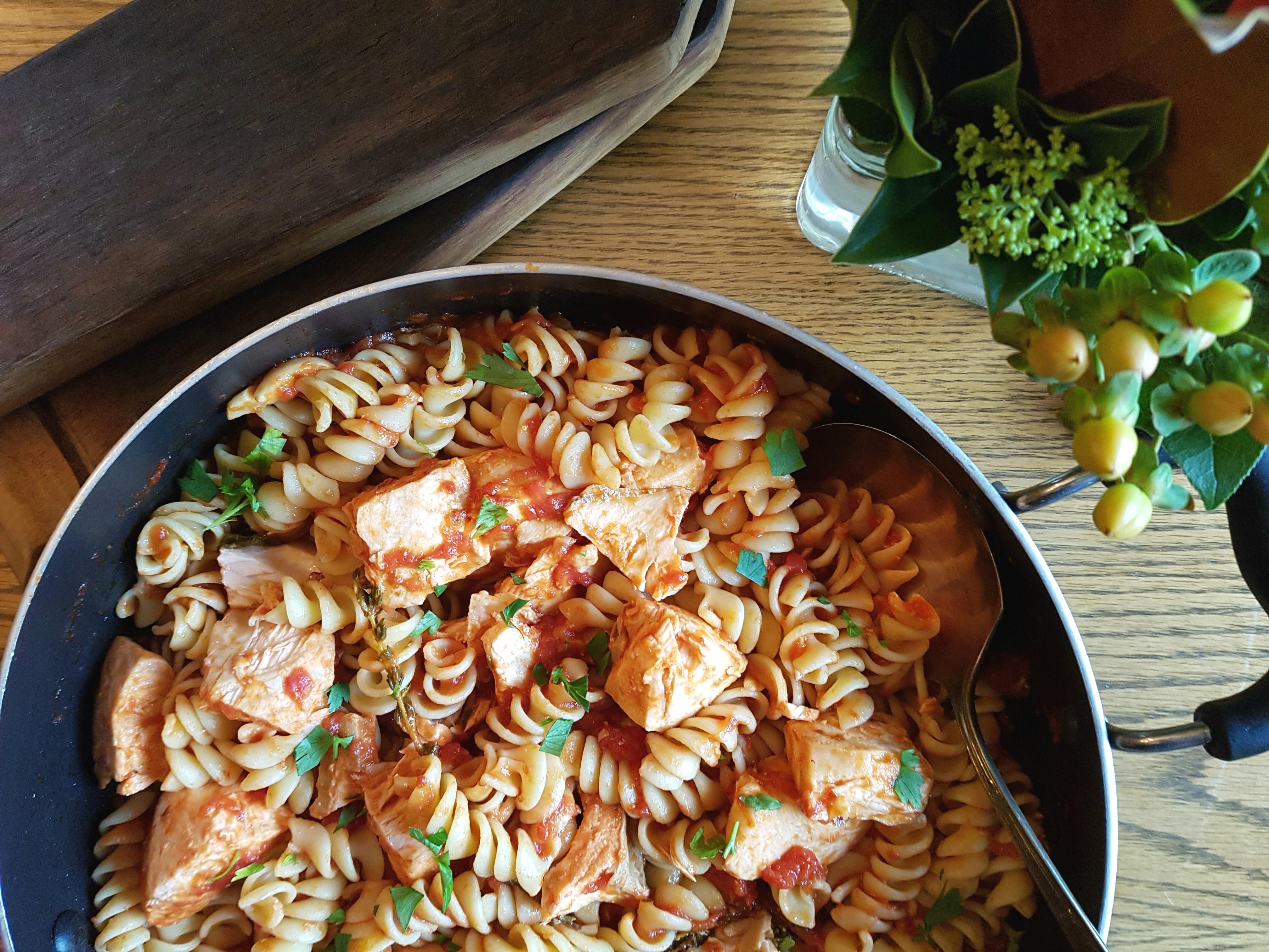 Cooked salmon, fusilli pasta, herbs in skillet