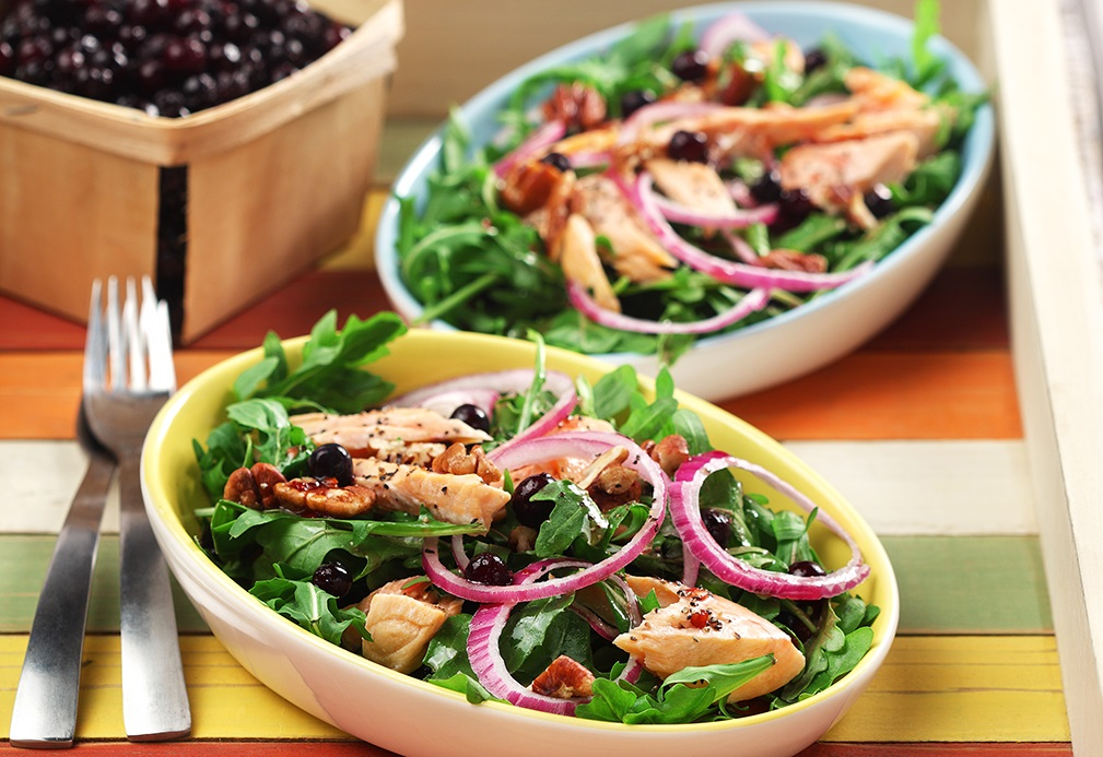 Bowls of arugula topped with cooked salmon, onion and blueberries