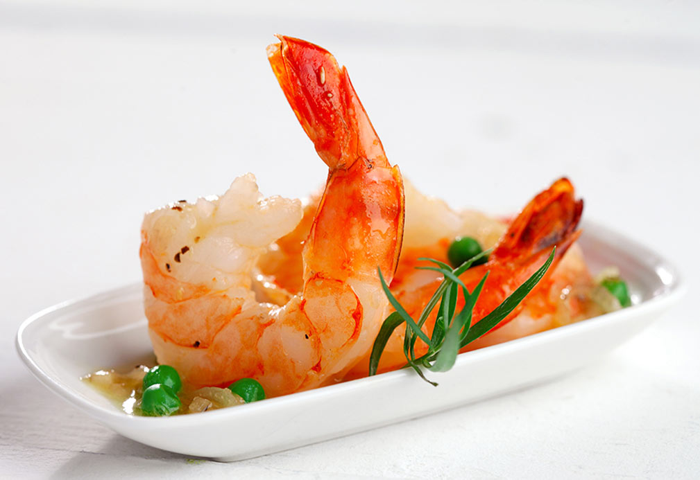Cooked shrimp and peas served on white plate