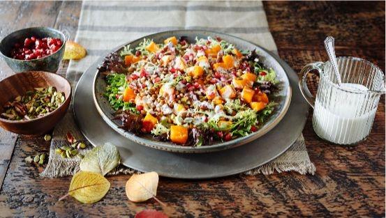 Roasted squash, lentils, arugula, pumpkin seeds, pomegranate salad in bowl
