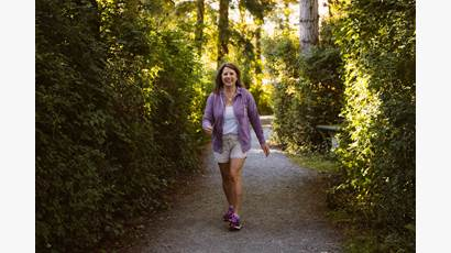 Tracy Bawtinheimer wears a purple jacket and shorts as she walks in the woods.