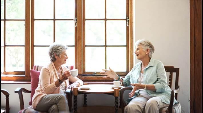 Two senior women talking and drinking tea