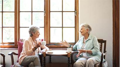 Two senior women talking and drinking tea