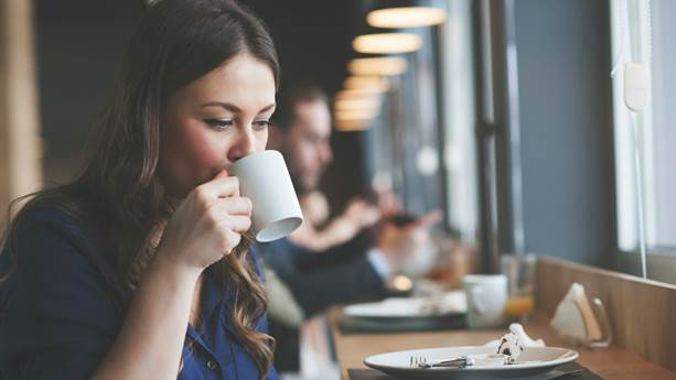 Woman sitting in a coffee shop sips from a white mug.