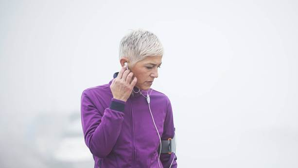 Woman listening to music while exercising outside