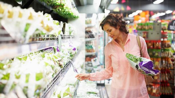 Woman in pink shirt buying lettuce in supermarket