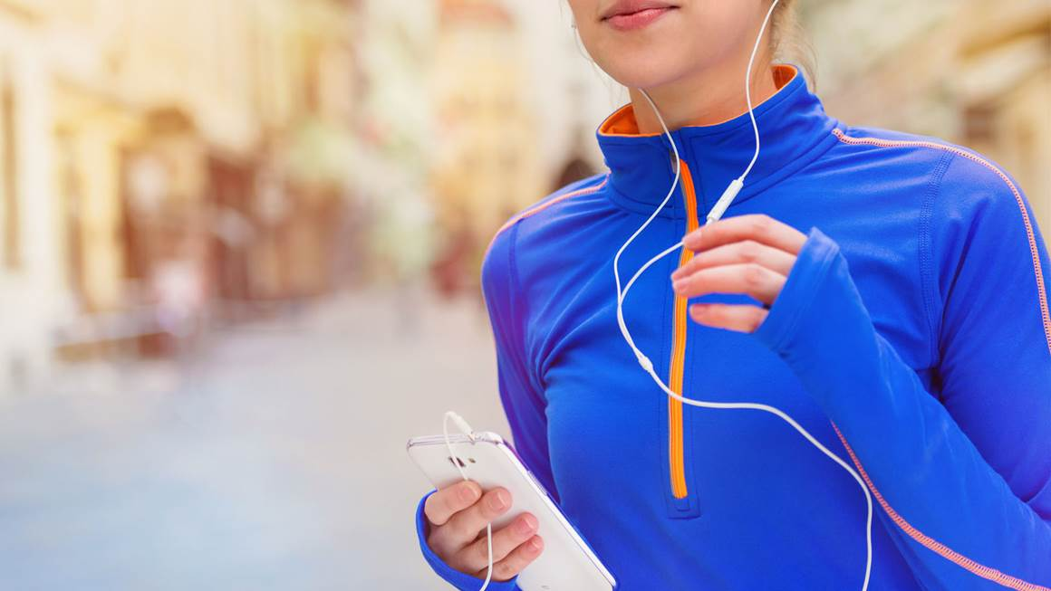 Woman jogging in city streets listening to music