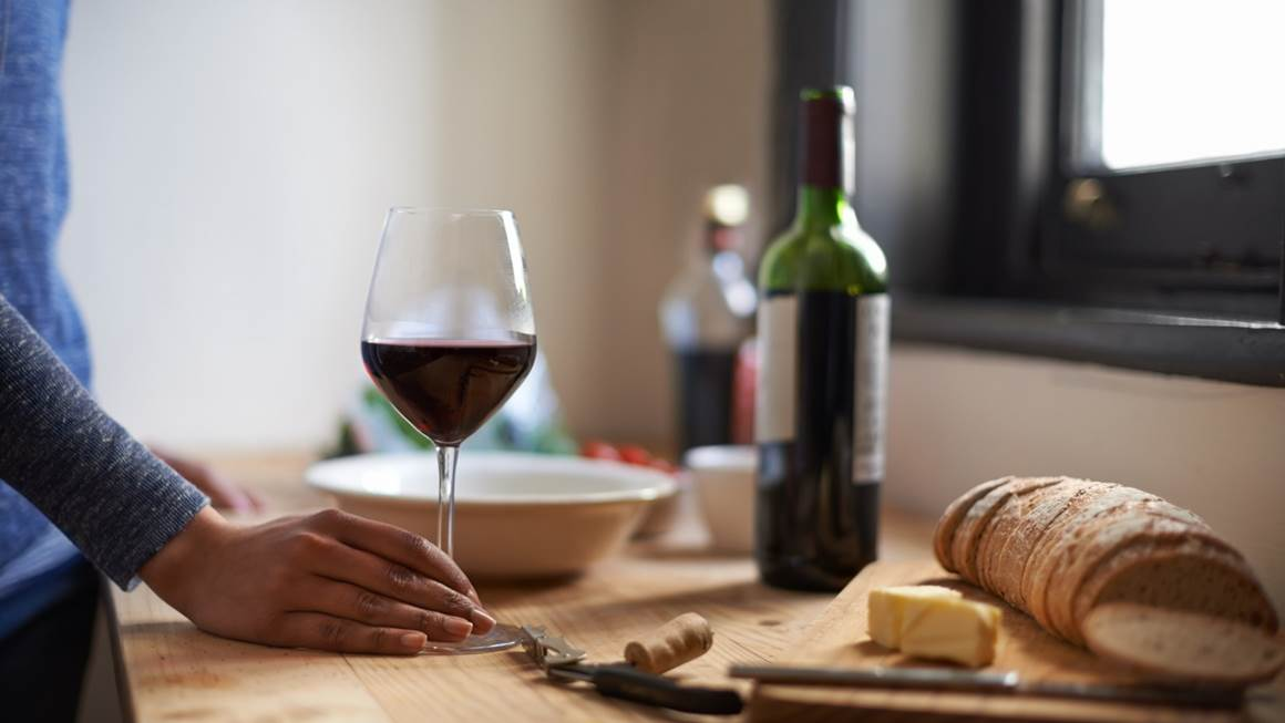 Woman standing at kitchen counter in front glass of red wine, bread and cheese