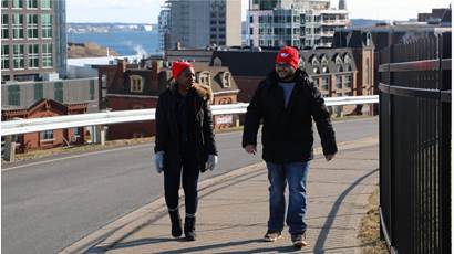 Two volunteers wearing red toques walk on a city street.
