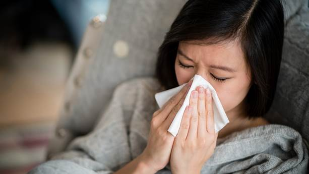A woman wearing a gray sweater blows her nose into a tissue.