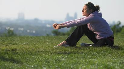 Young woman sitting on grass in sport clothes cityscape in background v2