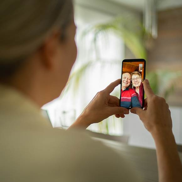 Smiling senior adult parents talking with daughter over mobile phone video call