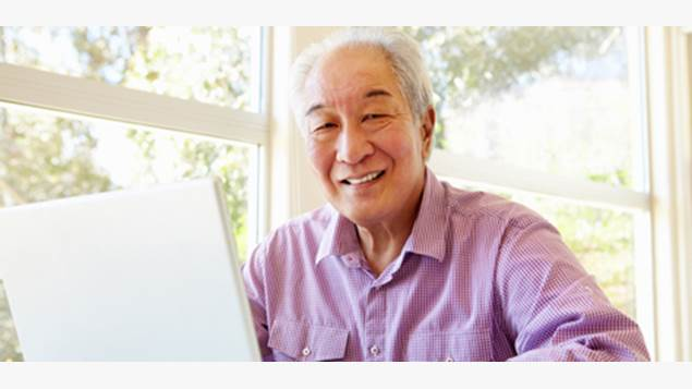 Man smiles as he sits by a computer
