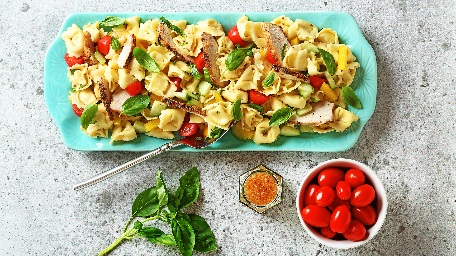 Chicken tortellini pasta salad on a blue serving platter with bowl of cherry tomatoes, dressing and a basil sprig on the side.