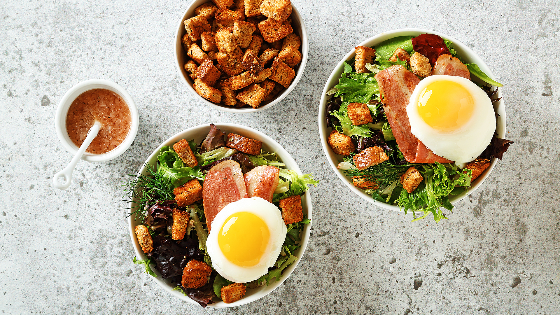 Bistro turkey bacon salad with a sunny side egg on top and a bowl of croutons on the side.