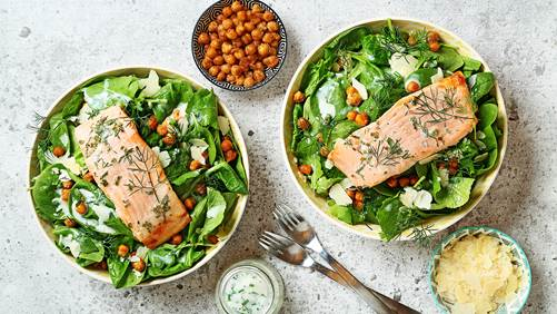 Kale chickpea salad with trout with silver utensils and bowls of chickpeas, dressing and parmesan cheese on the side.
