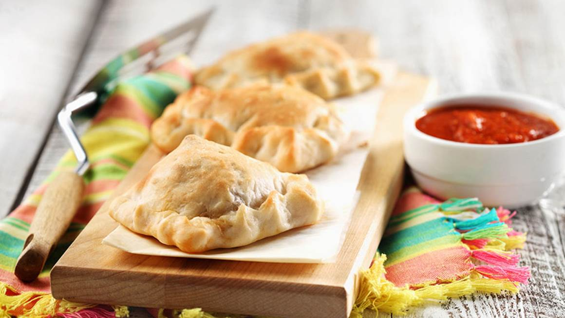 Mini calzones on a wooden serving board with red dip in a bowl on the side.