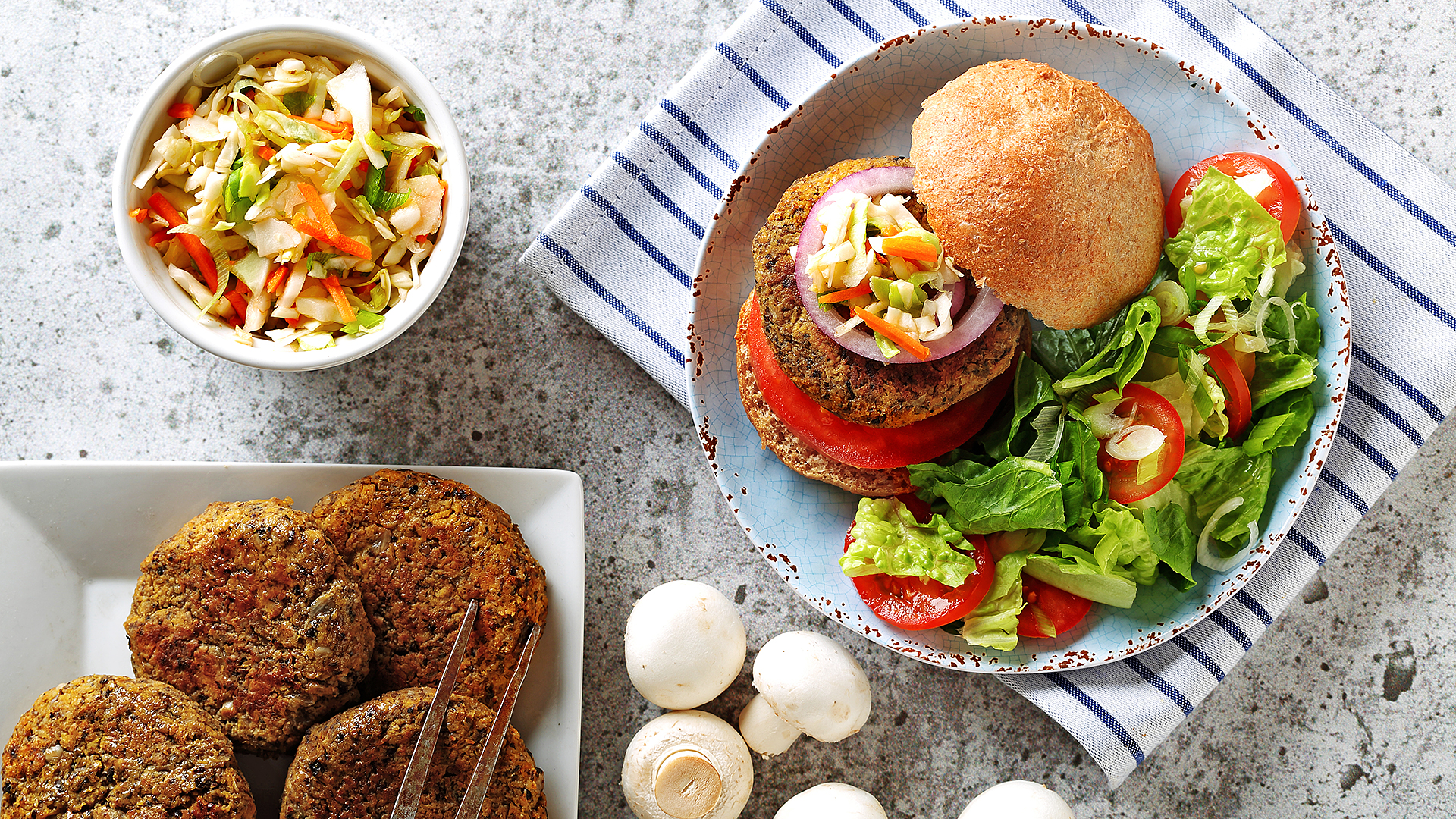 Mushroom squash burgers on a plate with a bun, salad, tomatoes and whole mushrooms on the side.