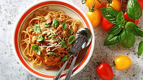 Roasted tomato sauce linguini in a serving bowl with silverware and whole tomatoes and basil clippings on the side.