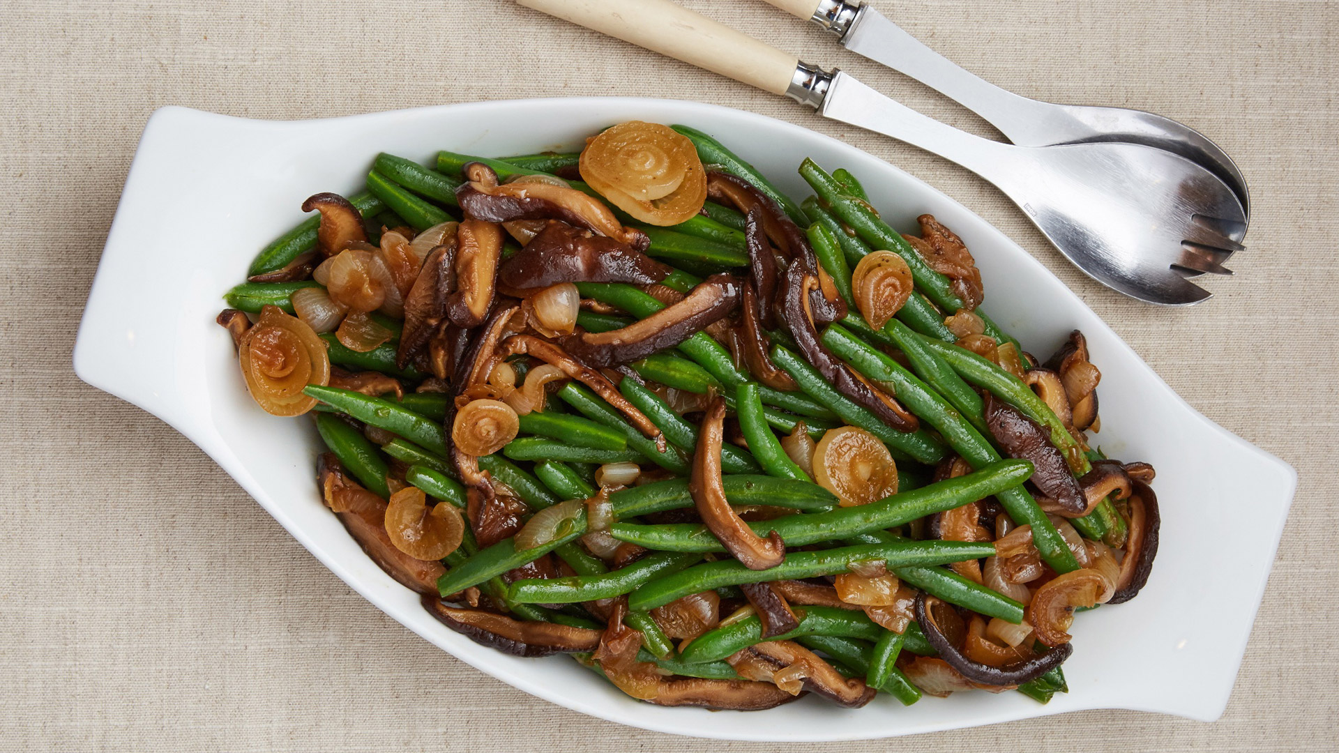 Asian green beans with wild mushrooms and Cipollini onions in a white serving dish and fork and spoon.