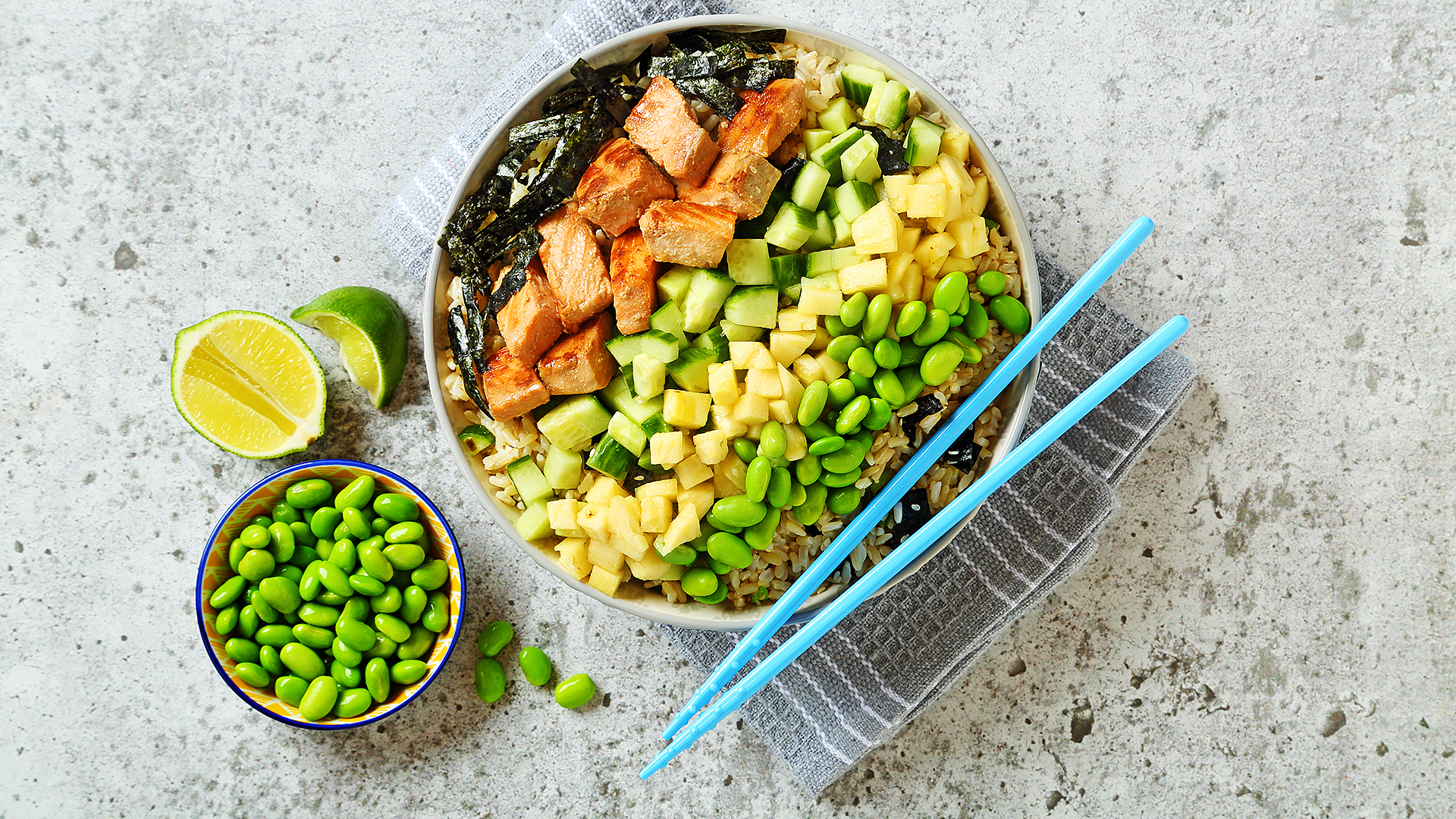Salmon poke style salad in a bowl with blue chopsticks and edamame and lime on the side