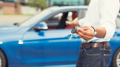 Man holding car keys in front of car