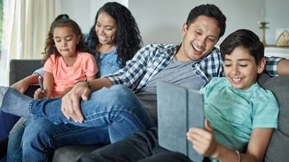 A smiling family of four sits on a couch while watching an iPad