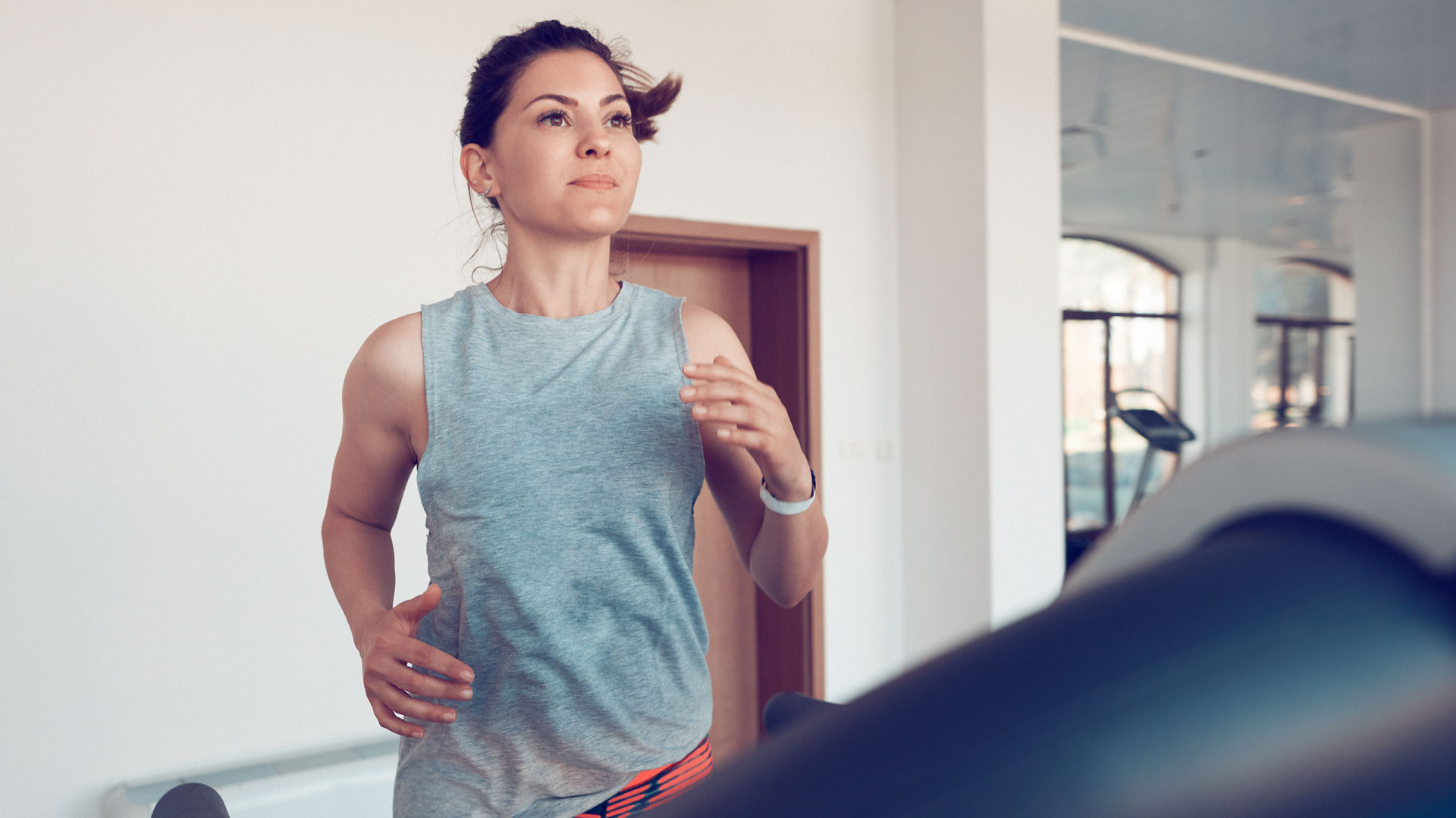 healthy and active woman running on treadmill, exercising inside gym.