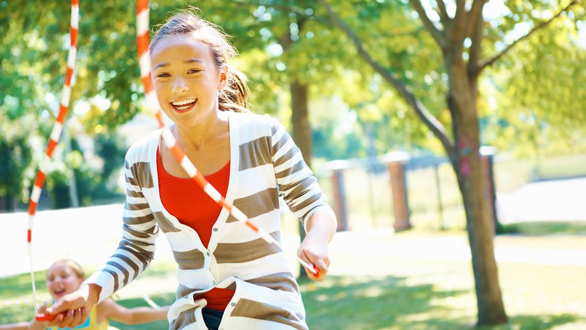 Young girl jumping rope outside