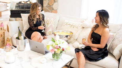Two women dressed up in black dresses while drinking champagne on a couch