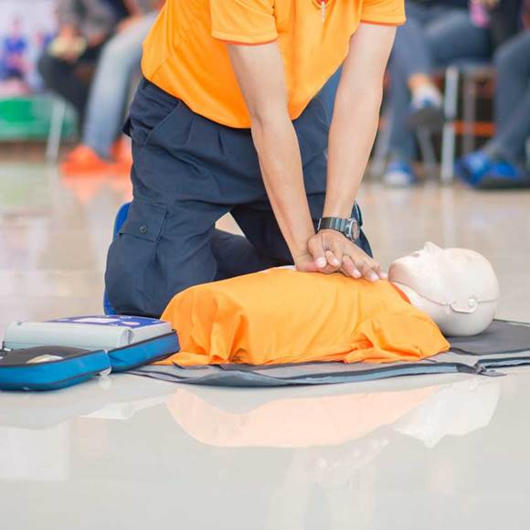CPR Training Demonstrating Chest Compression On A Dummy