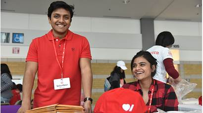 A man in a red t shirt and a woman in a red plaid button up smile while tabling at an event.