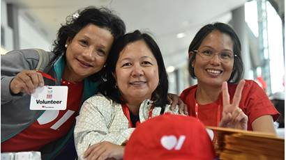 Three volunteers in Heart & Stroke t-shirts smiling.