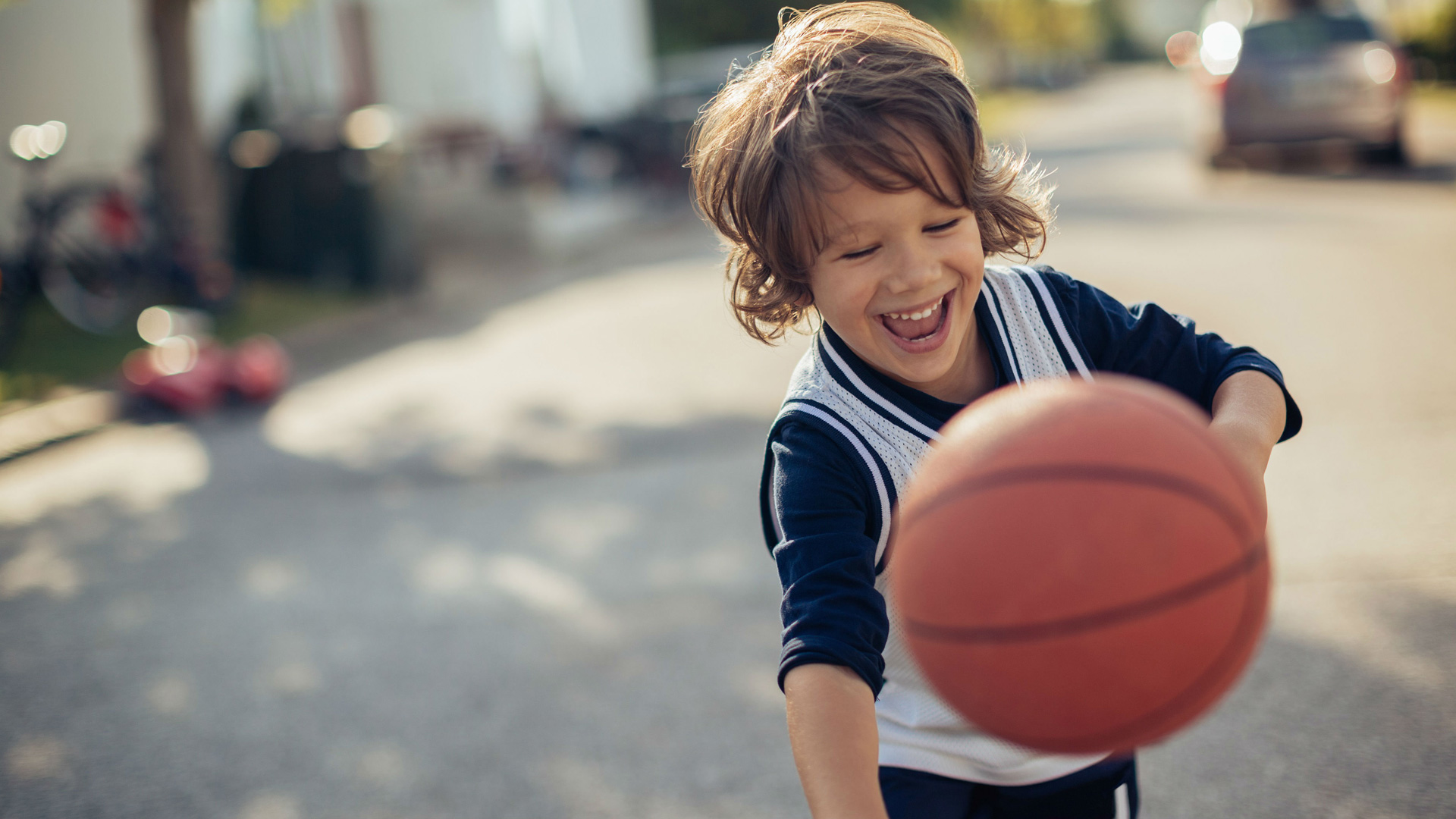 Little boy is smiling while  playing with a basketball on a suburban street