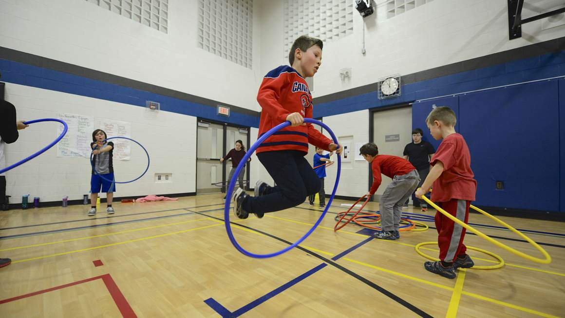 Boy jumping with hula hoop in gymnasium
